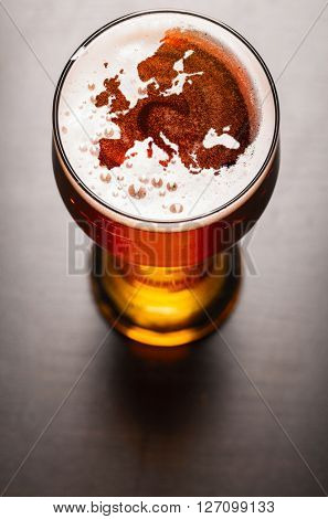 European beer concept, Europe silhouette on foam in beer glass on black table. The continents shapes are altered ones from visibleearth.nasa.gov