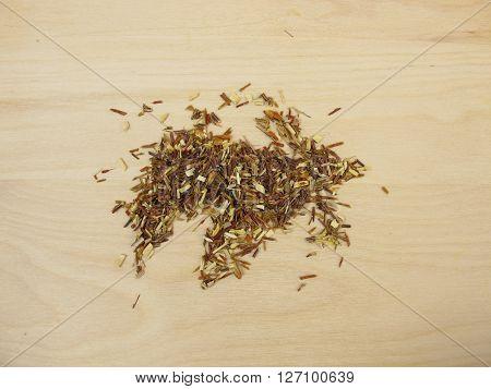 Loose green rooibos tea on wooden bard
