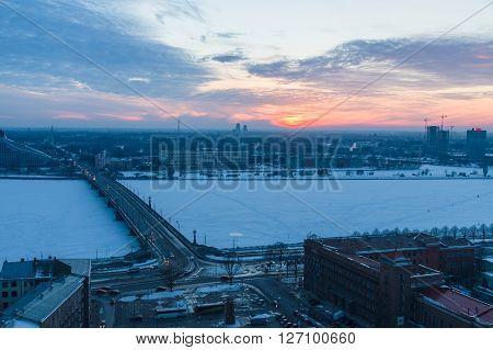 RIGA LATVIA - FEBRUARY 02: Winter-time sunset over Daugava river and Stone bridge. Construction of the bridge ended in 1957.