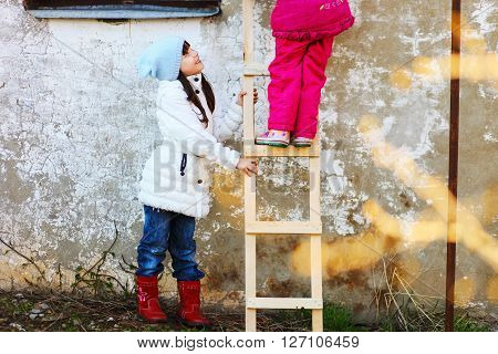 Children help each other to climb the ladder.