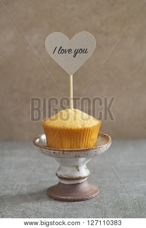 Homemade vanilla cupcake with a handcrafted Valentine day cake pick on rustic mini cake stand