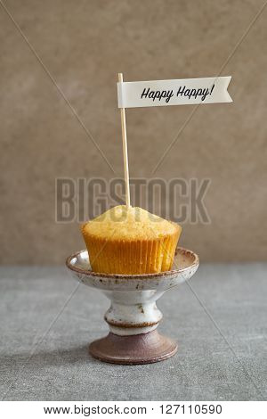 Homemade vanilla cupcake with a handcrafted birthday cake pick on rustic mini cake stand