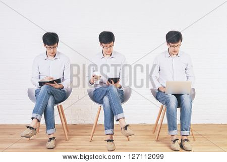 Brick interior with three different photos of one man organized into one picture collage. In the first picture the man is writing in the second one - using tablet in the third one - using a laptop