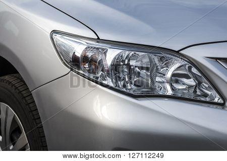 Closeup headlights . Modern luxury car close-up banner background. sports auto Closeup headlights