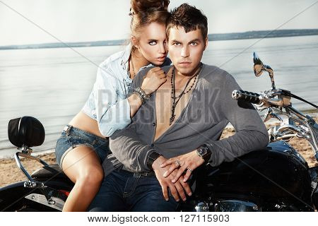 Attractive young couple on a motorcycle hugging.