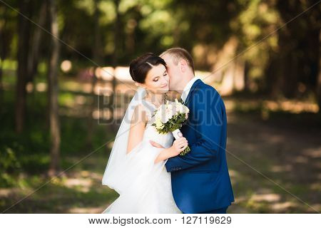 Beautiful brunette bride in elegant dress and handsome groom in blue suit at wedding day lovely hugging on summer nature. Bridal couple happy newlywed woman and man embracing in green park.