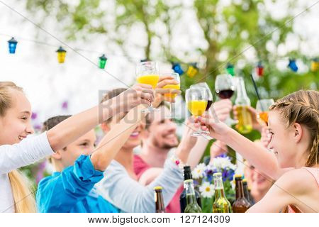 Friends and neighbors toasting on garden party