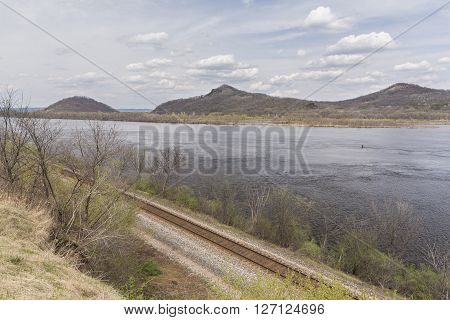 Mississippi River in spring with a railroad track in the foreground and hills in the background.