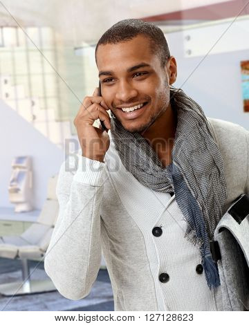Trendy casual afro american man talking on mobile phone at home. Smiling, standing.