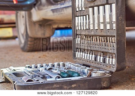 Toolbox for car repair. Mechanic is going to begin repairing the car. He has put his toolbox near a car