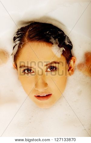 Young woman washing hair in bath