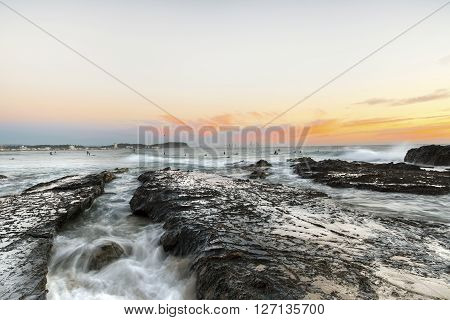 Surfers at Currumbin Rock Gold Coast at sunset, with ocean current rushing against a large rock
