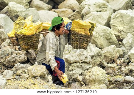 Ijen Crater, Indonesia - May 25, 2013: Sulfur miner carrying baskets with sulfur at Kawah Ijen volcano in East Java, Indonesia.