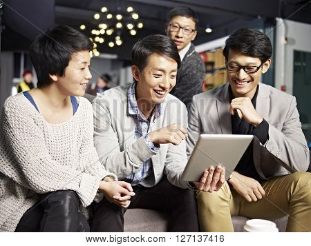 young asian businesspeople sitting in sofa looking at tablet computer happy and smiling. poster