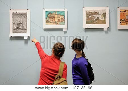 Orel Russia - April 22 2016: Girls looking at picture exhibition and specifies a hand