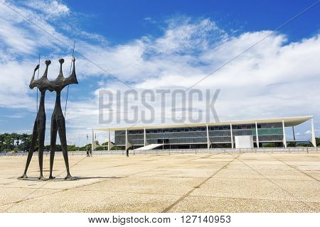 Brasilia, Brazil - November 18, 2015: Dois Candangos monument and Planalto Palace (Palacio do Planalto) building in Brasilia, capital of Brazil.