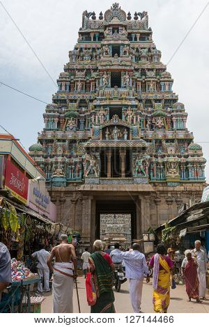 Trichy India - October 15 2013: One of the shorter gopurams near inner circle of Ranganathar Temple. Facade is set with statues. Pastel colors galore. People walking to gopuram.