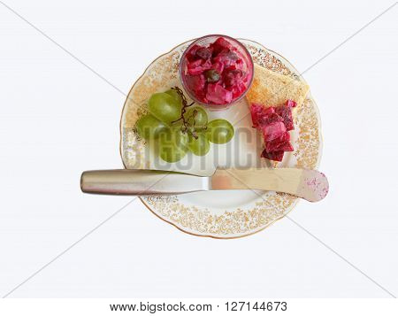 Herring salad in a glass and served with bread and grapes