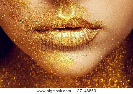 Magic Girl Portrait in Gold. Golden Makeup close-up portrait in studio shot color