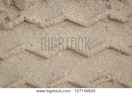 Truck tire tracks through the sand tire design features a zigzag pattern.