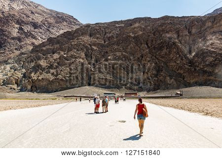 DEATH VALLEY, CALIFORNIA - SEPTEMBER 9, 2015: View of the Badwater Basin in the Death Valley National Park on September 9, 2015. Tourist walking on the hot playa.