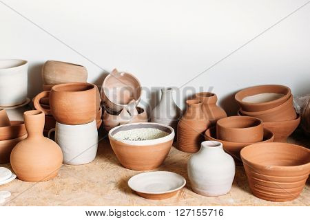Antique clay crockery set  on white background. Many handmade ceramics objects on wooden shelf. Brown clay crockery in pottery workshop.