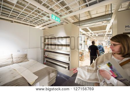 PARIS FRANCE - APR 12 2016: Woman choosing mattress bed in the decorated store of IKEA Furniture amll store in Paris France