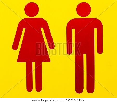 male and female as often used to indicate restrooms with two silhouetted figures standing side by side on yellow