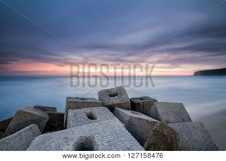 sunset from stone jetty and cliff on background in Cadiz Spain