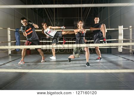 group of people practicing body combat attack in boxing ring