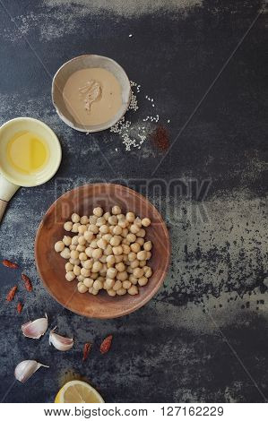 Preparing homemade hummus. Ingredients for hummus on dark concrete background.  Top view, vintage toned image, blank space