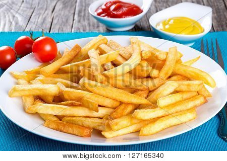 Tasty french fries on white plate on wooden table background blank space left top view close-up