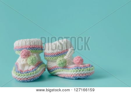 Newborn Announcement. Knitted Baby Booties On Plain Aquamarine Background