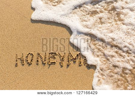 Honeymoon - inscription by hand on sea sand washed off the oncoming wave.