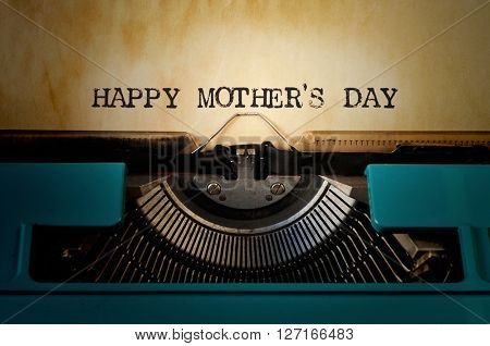 closeup of an old blue typewriter and the text happy mothers day typewritten with it in a yellowish foil