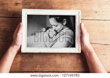 Mothers day composition. Hands of unrecognizable man holding a picture of mother and baby daughter. Studio shot on wooden background.