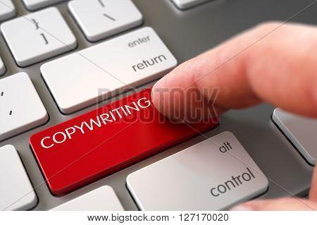 Hand Touching Copywriting Key. Close Up view of Male Hand Touching Copywriting Computer Button. Man Finger Pushing Copywriting Red Button on Metallic Keyboard. Copywriting Concept.