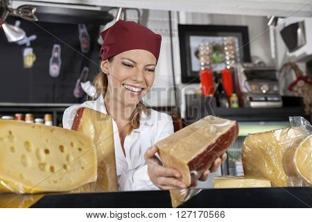 Saleswoman Holding Piece Of Cheese In Grocery Store