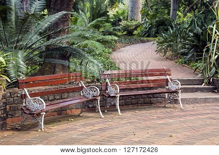 Two Vintage Park Benches On Paved Brick Walkway