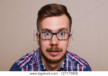 Face of the surprised man. A young man in glasses and a shirt with a surprised look into the camera. Guy with wide open eyes with glasses a beard and mustache.