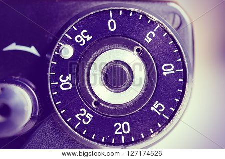 Fragment of old film camera. Top view of shutter button and the frame counter. Close up view. Macro. Selective focu. sVintage photo. Toning. poster