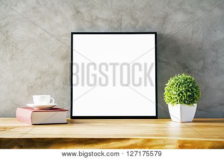 Closeup of wooden table with blank frame flowerpot coffee cup and book on concrete background. Mock up