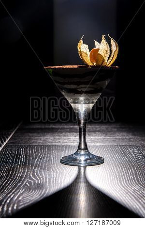 tiramisu dessert in glass on black wooden table