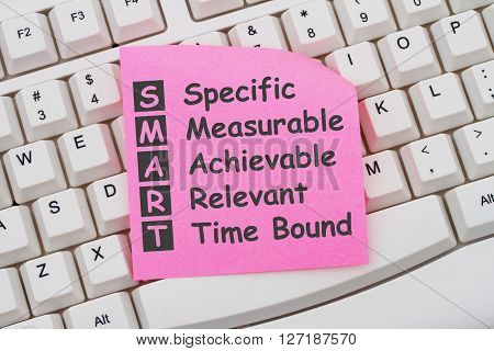 Writing your SMART Goals Computer Keyboard with a pink sticky note with text listing SMART Goals
