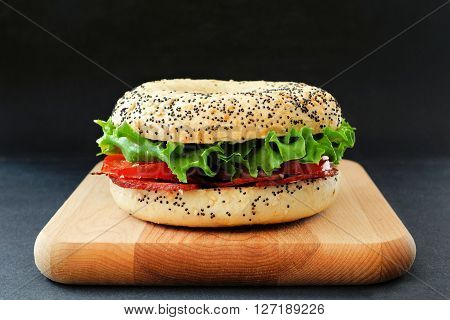 Blt Bagel Sandwich With Turkey Bacon On A Wood Board Against Slate Background