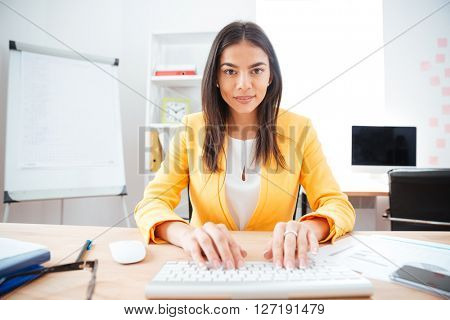 Happy charming businesswoman typing on keyboard in office