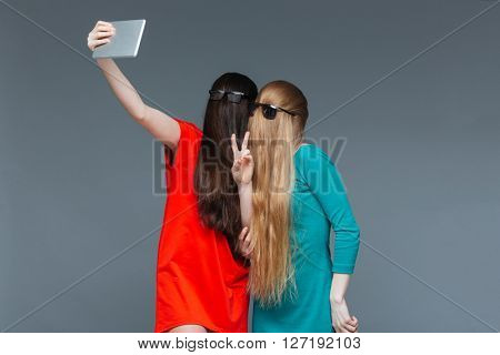 Two comical young women with faces covered by long hair taking selfie with tablet over grey background