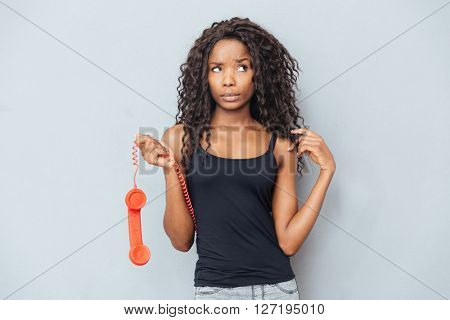 Pensive woman holding retro phone tube and looking away at copyspace over gray background