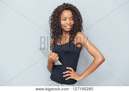Happy afro american woman standing with tablet computer over gray background and looking away