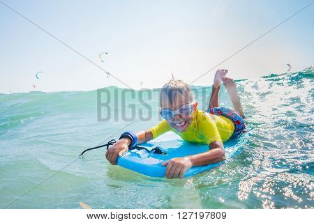 Little boy with surf board having fun in sea against sea ** Note: Visible grain at 100%, best at smaller sizes